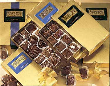 Assorted dark chocolates in a gold box.